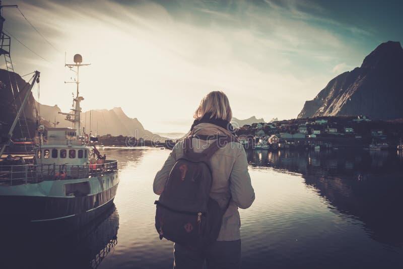 看日落的妇女旅客在雷讷村庄,挪威 免版税图库摄影