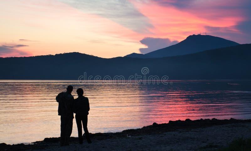看日落的男人和妇女 免版税图库摄影