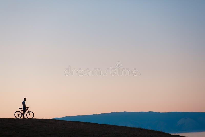看日落的骑自行车者 免版税库存照片