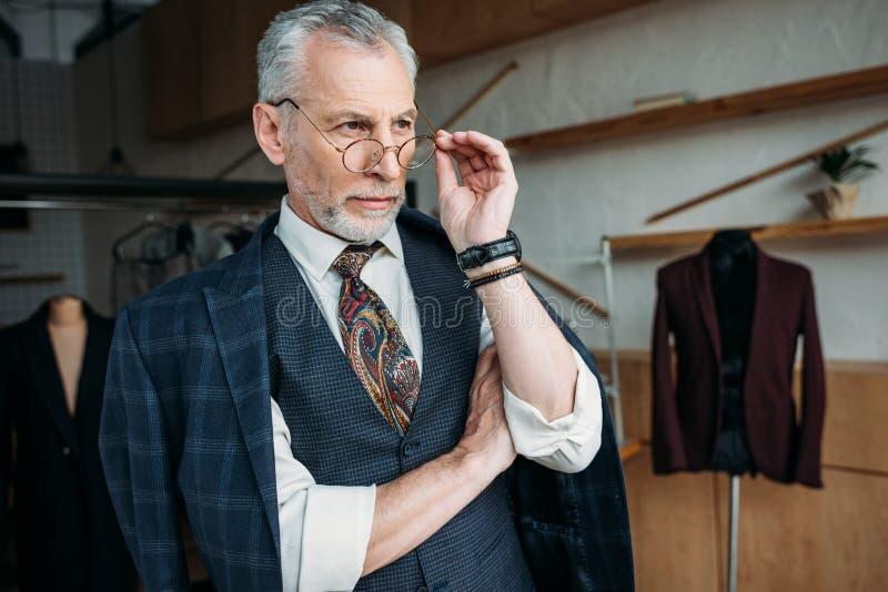看时髦的衣物的确信的成熟裁缝  免版税库存照片