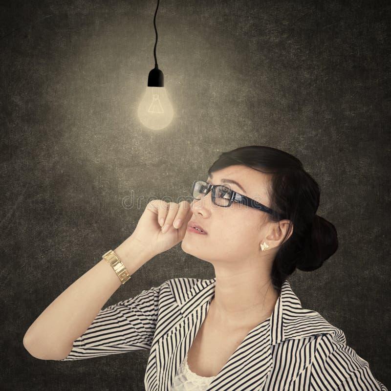看明亮的电灯泡1的女实业家 图库摄影