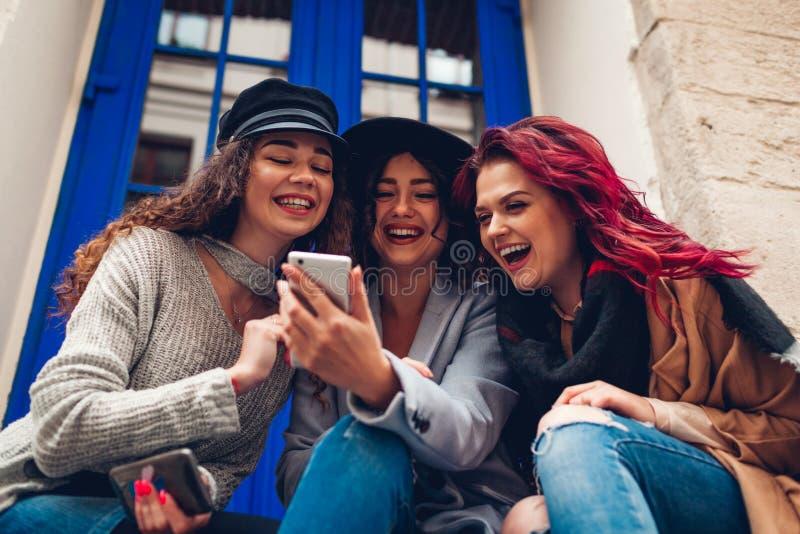 看智能手机和笑由咖啡馆的三个少妇室外射击  有乐趣的女孩联系 库存照片
