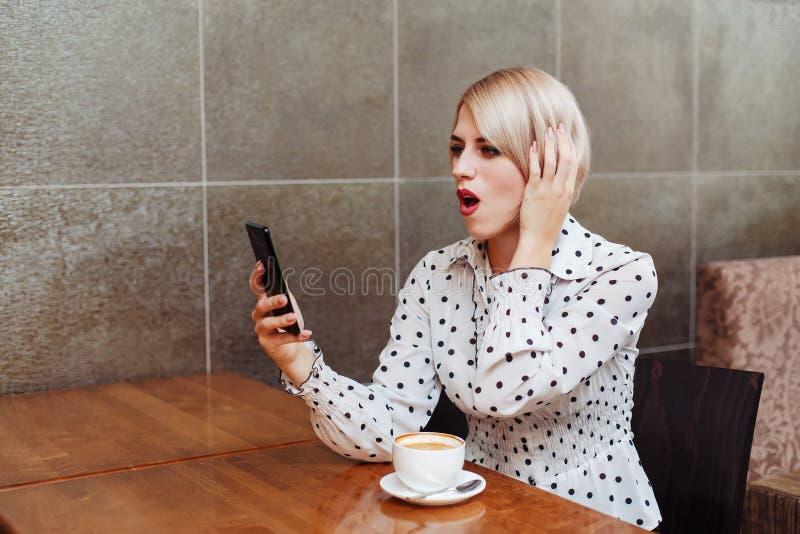 看智能手机的咖啡馆的惊奇的妇女 图库摄影