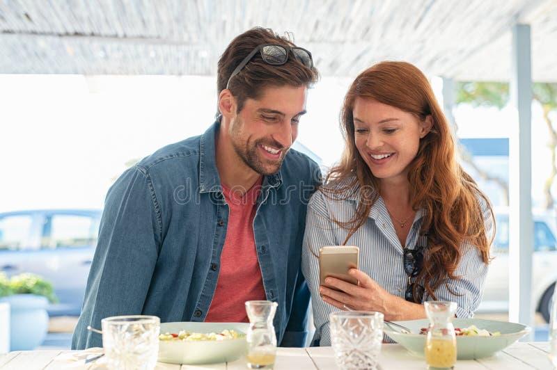 看智能手机的年轻夫妇 免版税库存图片