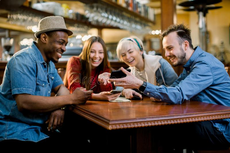 看智能手机的快乐的年轻朋友画象,当坐在咖啡馆时 参加在桌上的混合的族种人  库存照片