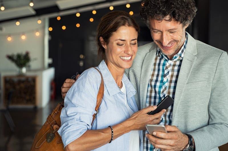 看智能手机的成熟夫妇 库存图片