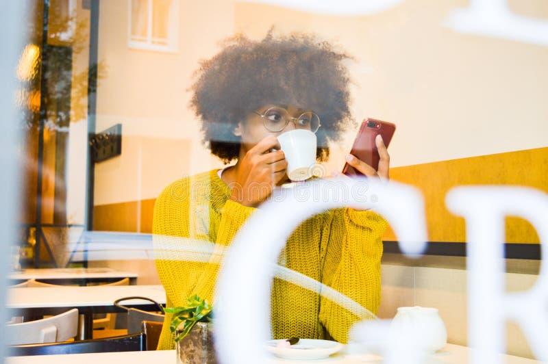 看智能手机饮用的咖啡的美丽的年轻黑人妇女咖啡厅 库存照片
