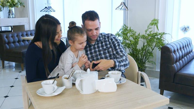 看智能手机,谈论和微笑的愉快的年轻家庭 免版税库存图片