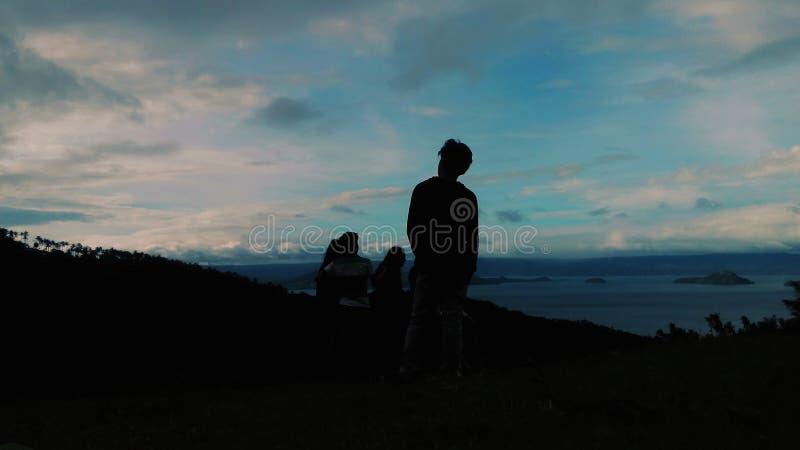 看有他的朋友的一个十几岁的男孩的剪影Taal湖 免版税库存照片
