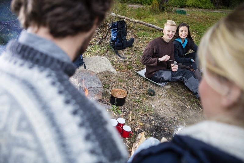 看朋友的愉快的夫妇在野营期间 免版税图库摄影