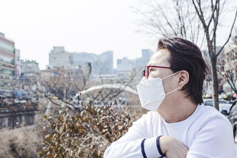 看朦胧的天空的亚裔妇女 佩带的保护面具 免版税图库摄影