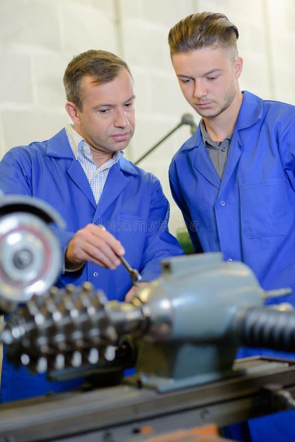 看机械零件的工程师和学徒 库存照片