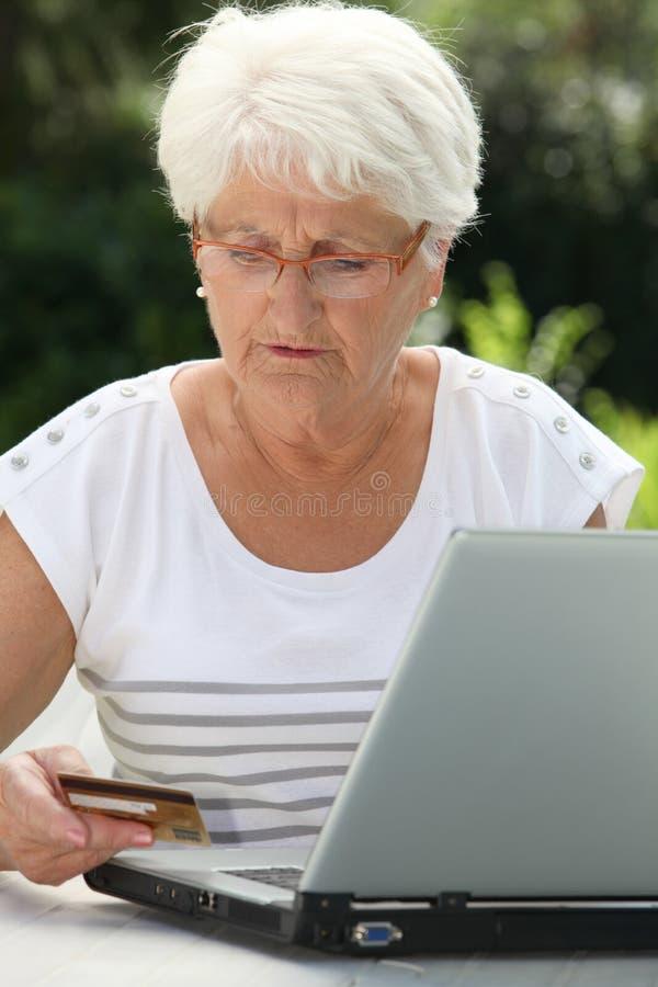 看板卡使用妇女的赊帐年长的人 库存照片