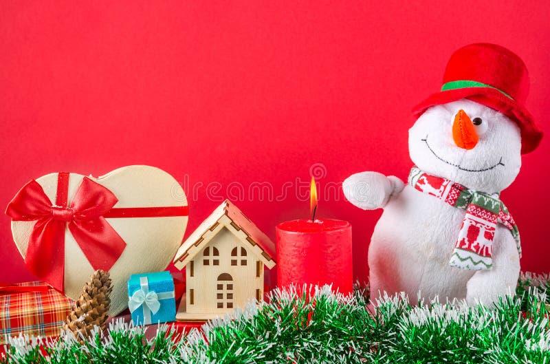 看板卡圣诞节新年度 与灼烧的蜡烛,锥体,在绿色闪亮金属片的giftbox的滑稽的雪人反对红色背景 图库摄影
