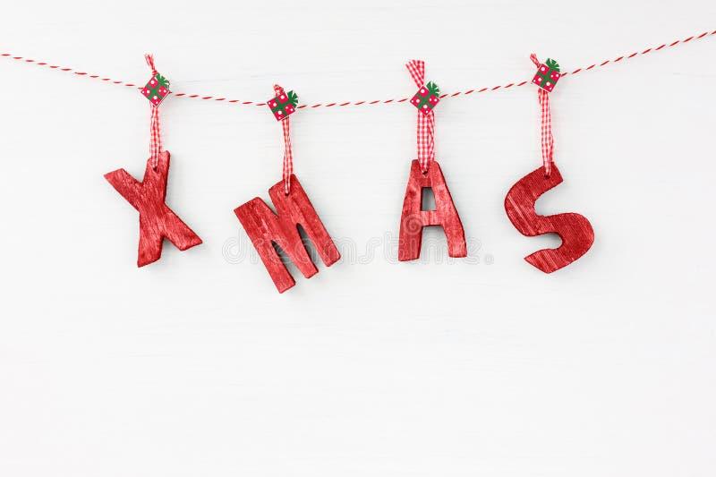 看板卡圣诞节问候 形成词XMAS的红色木信件 C 库存照片