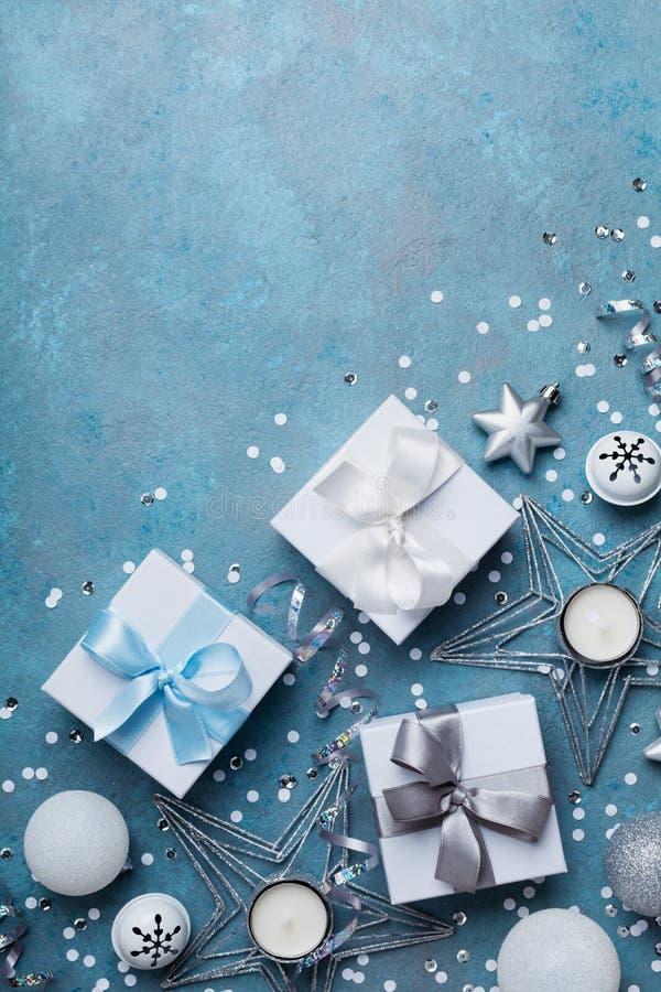 看板卡快活圣诞节的问候 礼物盒和假日装饰在蓝色台式视图 平的位置 免版税库存图片