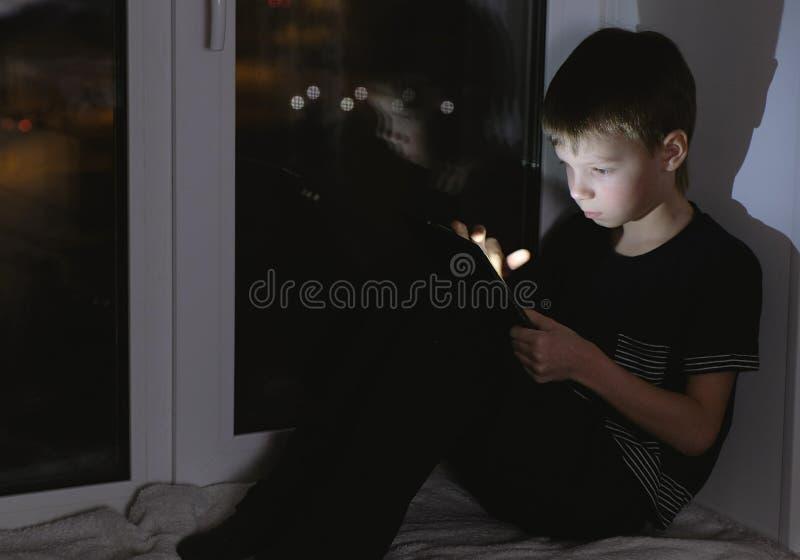 看某事在片剂的七岁的男孩 坐在黑暗的窗台在晚上 图库摄影
