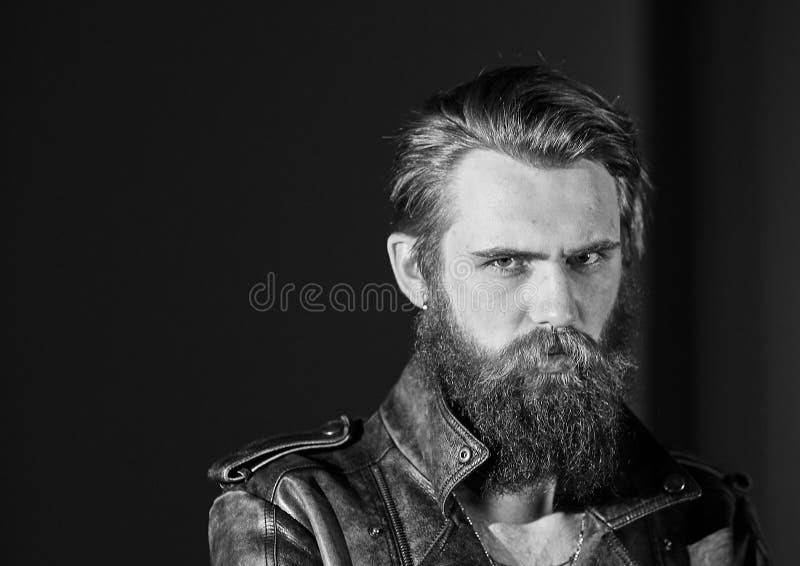 看某处对的皮夹克的严肃的有胡子的人 库存照片