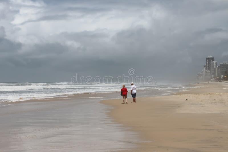 看横跨海滩的戈尔德比尤特-冲浪者天堂风雨如磐的海洋的不可能验明的游人在昆士兰澳大利亚 库存照片