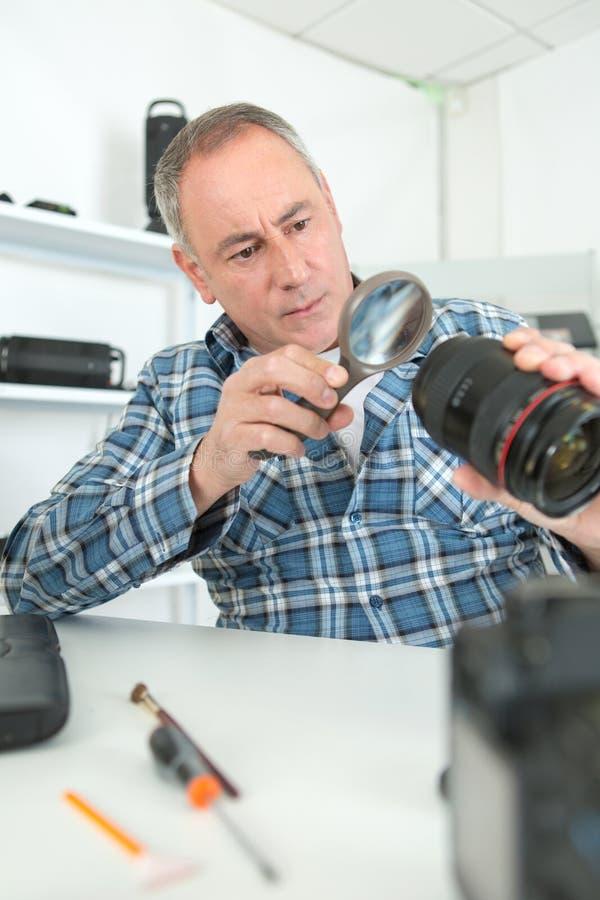看残破的摄影lense的人 免版税库存照片