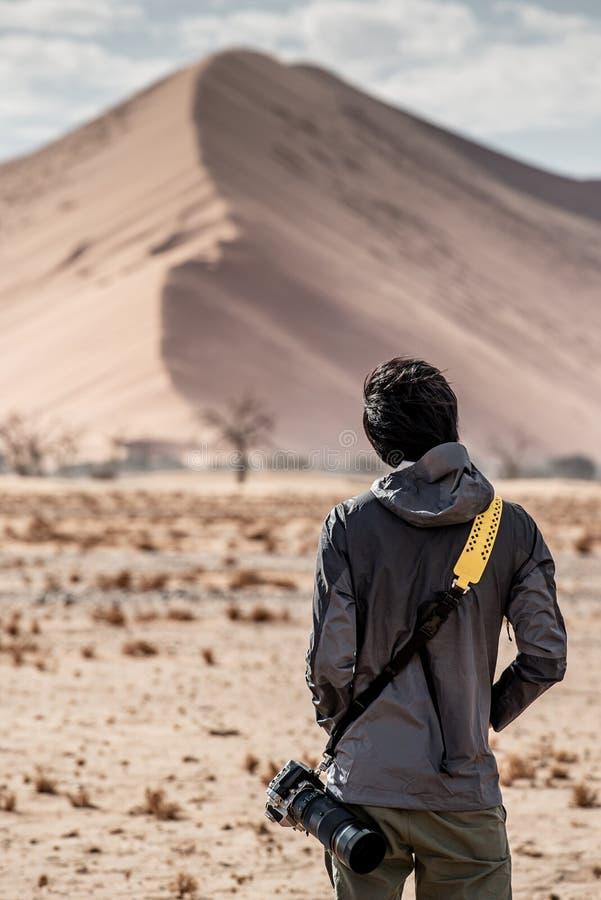 看沙丘的亚裔摄影师在沙漠 库存图片