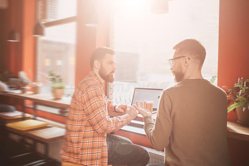 看法两个最好的朋友坐在桌上并且有交谈的地方 他们在一美丽晴朗的咖啡馆 免版税图库摄影