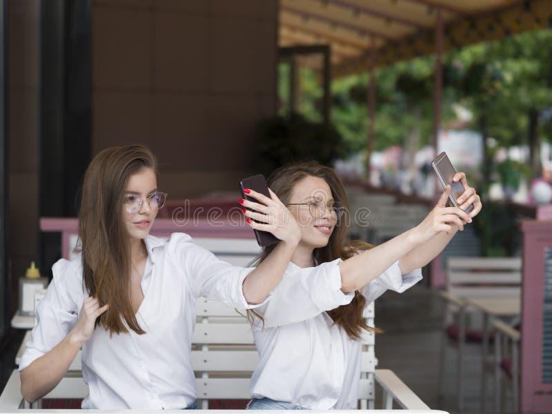 看法两个逗人喜爱的女孩采取selfie,当坐在夏天咖啡馆时 会议和友谊概念 ?? 免版税库存图片