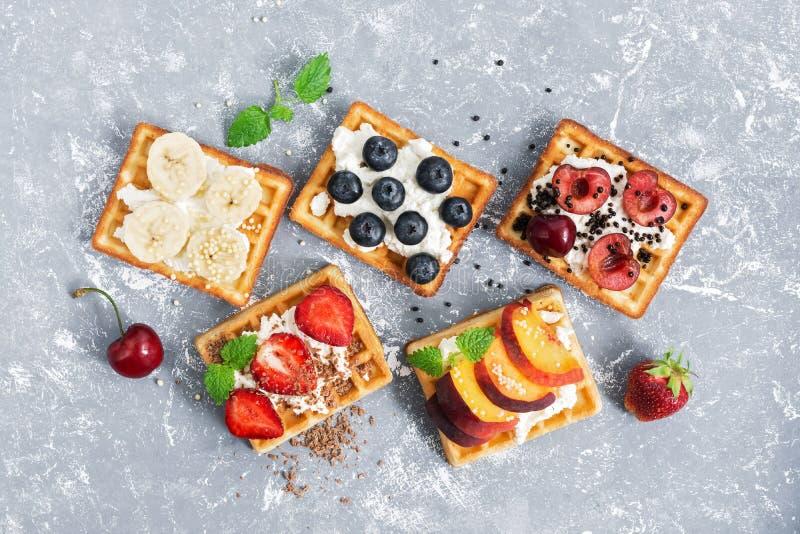 看法从上面与果子和莓果奶油的一个薄酥饼在灰色背景 传统比利时华夫饼干 库存图片