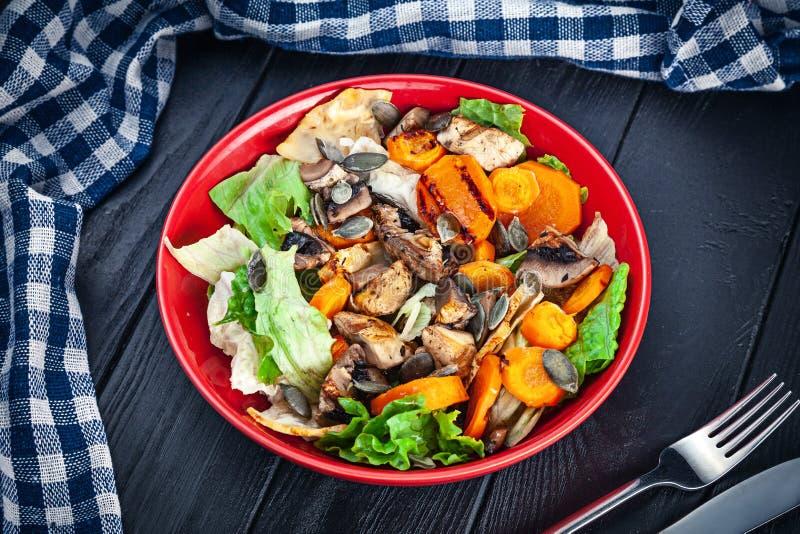 看法从上面在新鲜,自创素食主义者碗 红萝卜,蘑菇,在橙色碗的莴苣素食沙拉在黑暗木 免版税图库摄影