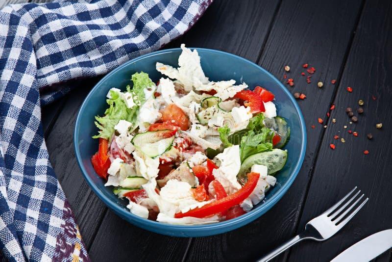 看法从上面在新鲜,自创素食主义者碗 蕃茄莴苣素食沙拉在蓝色碗的在黑暗的木背景 ?? 库存图片