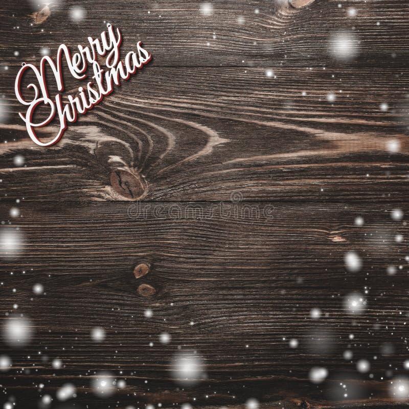 看法从上面在木背景,与空间的贺卡的圣诞快乐题字文本文字的,雪作用 图库摄影