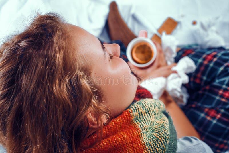 看法从上面在病的妇女在拿着一杯茶的床上用在它的桔子 免版税库存图片