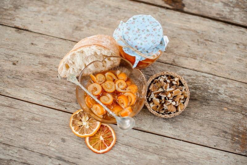 看法从上面在糖煮的橙色螺旋果皮用在玻璃瓶子和板材的糖浆在茶碟附近用核桃 免版税库存照片