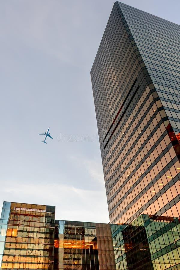 看法从下面向上在玻璃现代摩天大楼和飞行的a 库存图片