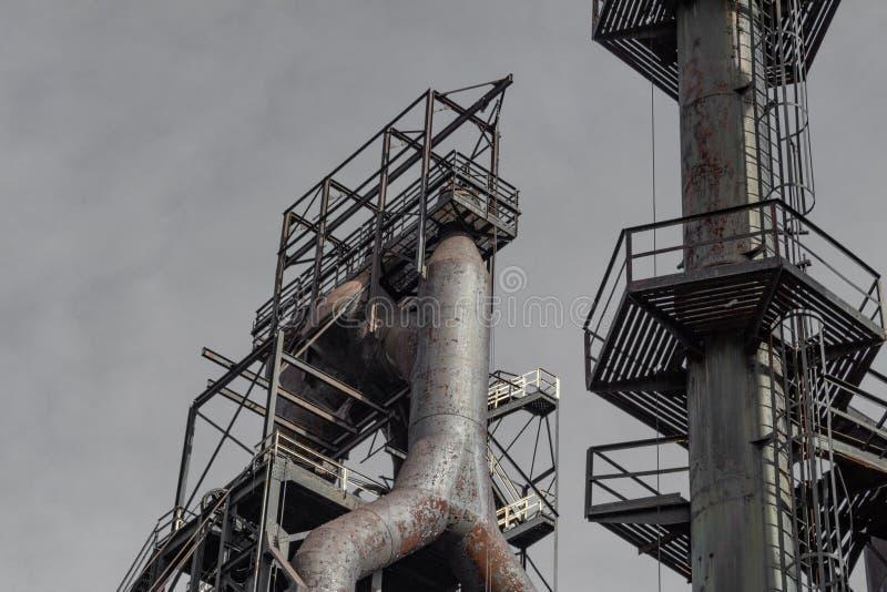 看法从下面鼓风炉和烟窗在老钢铁厂复合体 库存照片