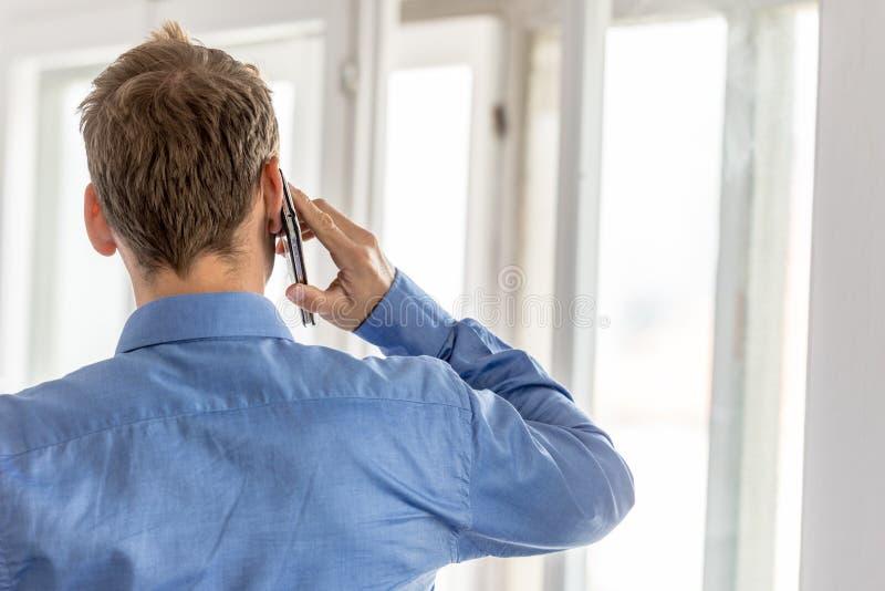 看法从后面商人谈话在一个手机 库存图片