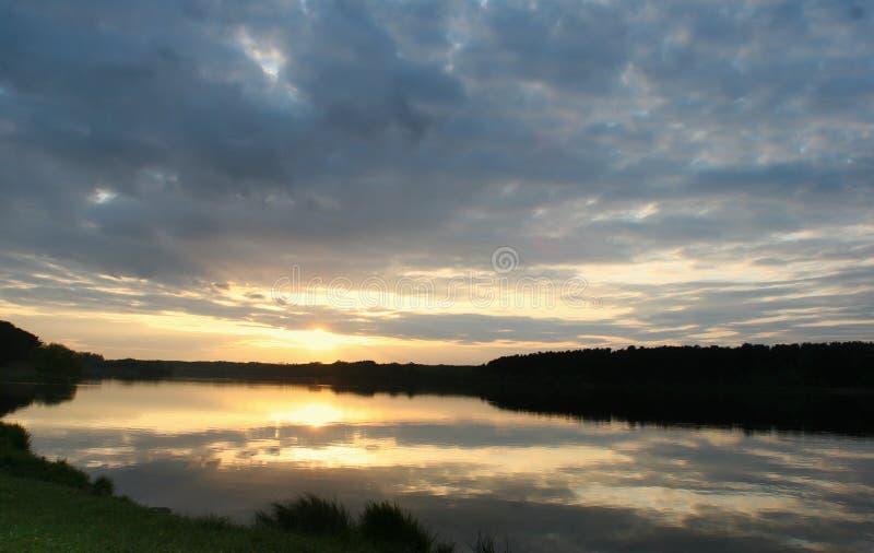 看法向有反射和蓝色多云天空的河 免版税库存照片