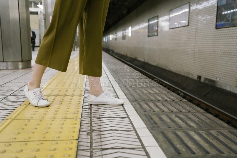 看法女孩` s腿和等待的火车来 库存图片