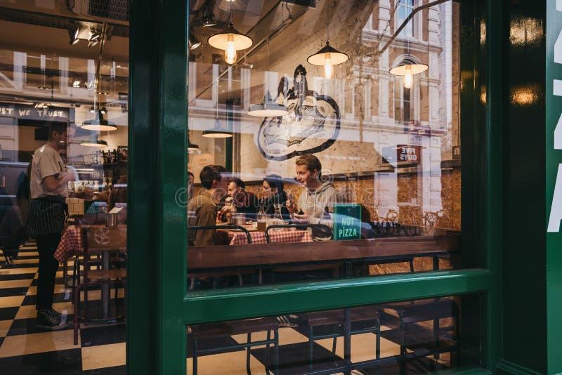 看法通过人窗口在一家餐馆里面的在科文特花园,伦敦,英国 免版税图库摄影