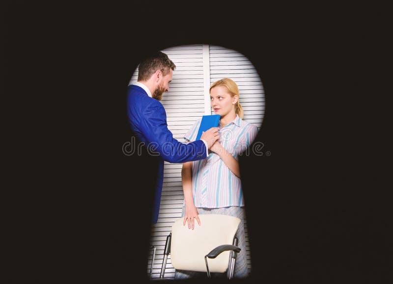 看法通过匙孔 上司积极的威胁的暴力 办公室罪行的证人 妇女在办公室遭受暴力 库存图片