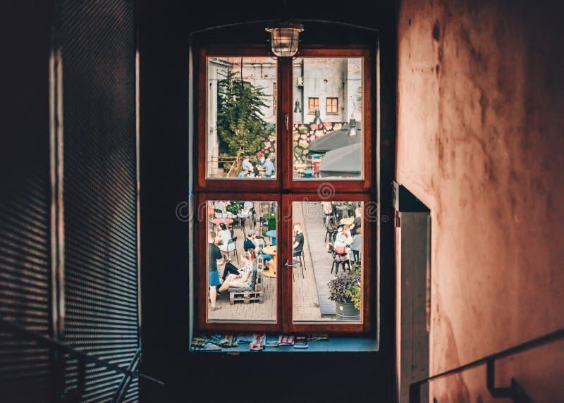 看法通过在坐在啤酒庭院里的年轻人的小窗口在克拉科夫,波兰 r 库存照片