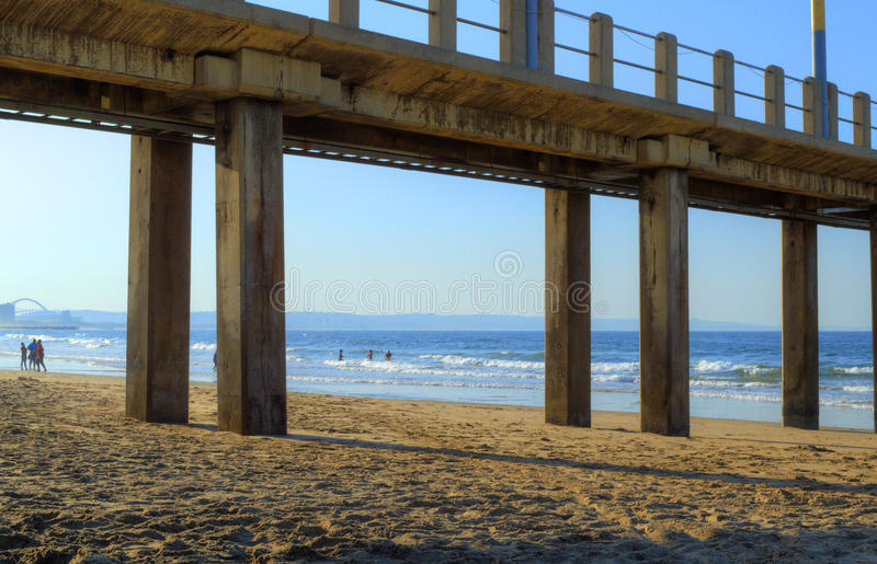 看法通过在黄昏的一个码头在金黄英里海滩,德班,南非 免版税库存图片