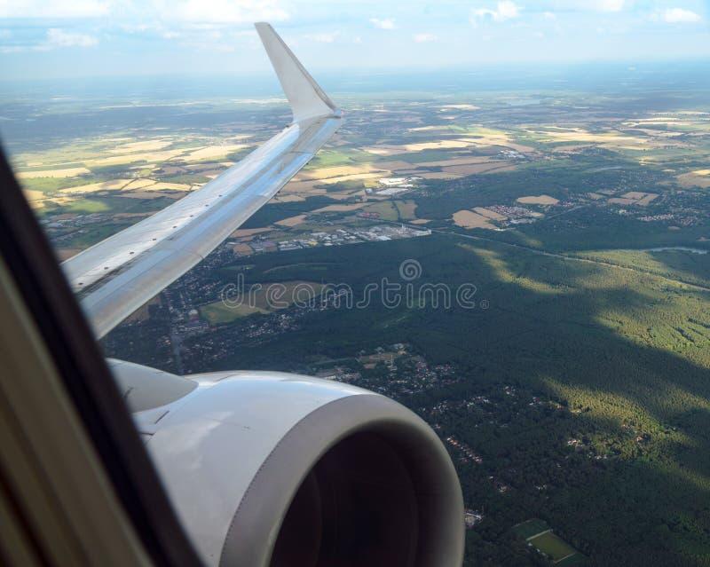 看法通过对翼和喷气机引擎的一个飞机窗口在一个农业风景,旅行概念 库存照片