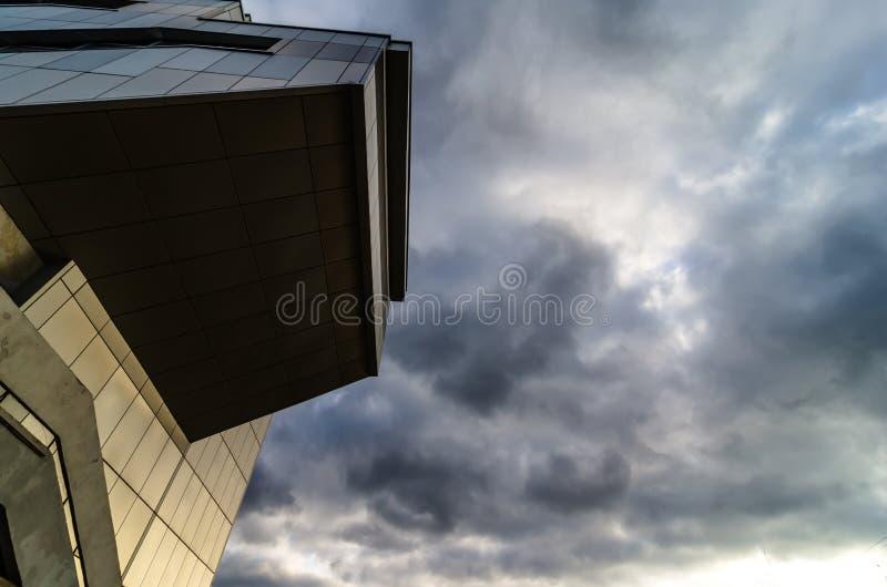 看法通过现代高上升的摩天大楼向上对与白色云彩的蓝天-抽象建筑学细节背景 库存图片