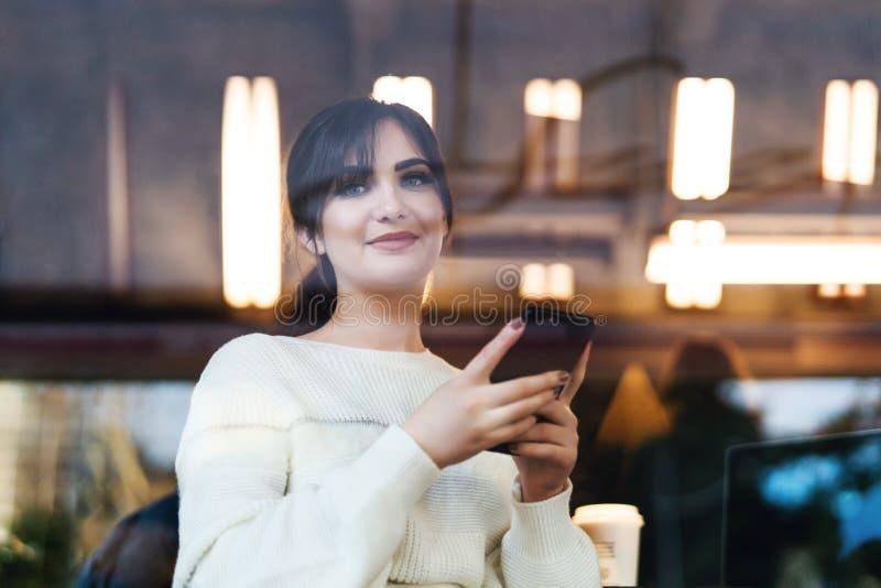 看法通过玻璃容器 微笑的年轻女人画象有智能手机的在她的手上,坐在桌咖啡馆,看照相机 免版税图库摄影