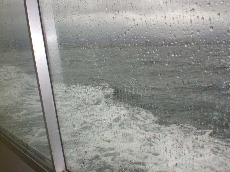 看法通过落入海的多雨窗口 滚动沿玻璃的下落 库存图片