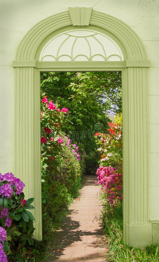 看法通过被成拱形的门,开花的杜鹃花 库存照片