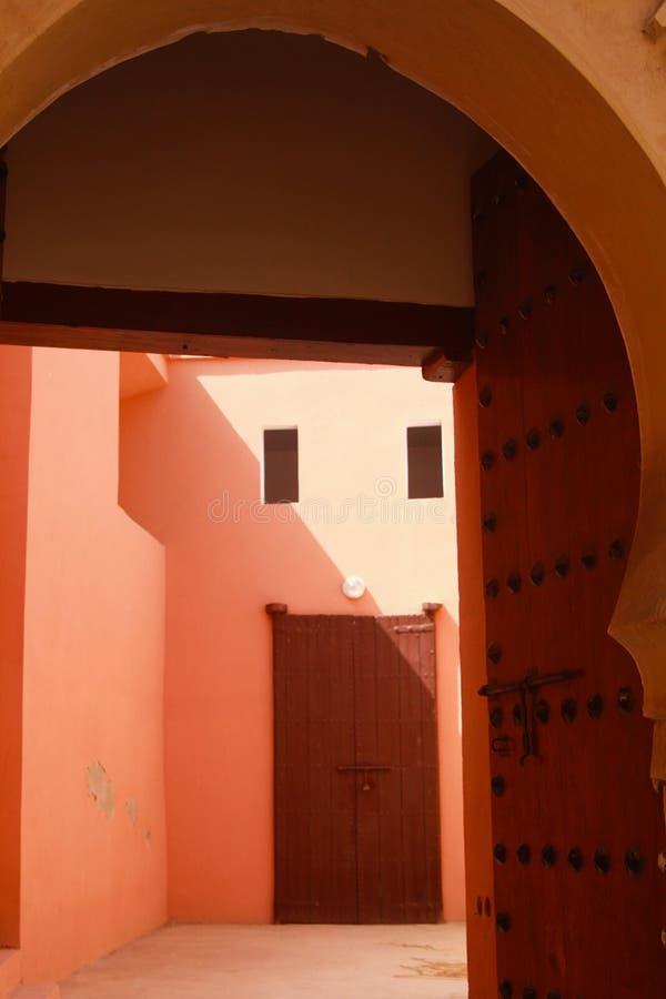 看法通过阿拉伯样式曲拱到在红橙色光的明亮的晴朗的空的前院胡同里与老木门 免版税库存照片