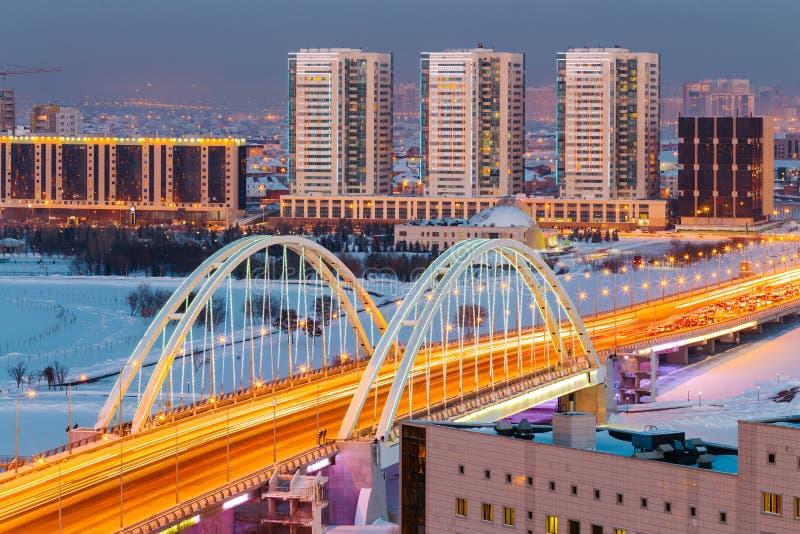 看法从上面在横跨伊希姆河的M1桥梁在一个冬天晚上在阿斯塔纳,哈萨克斯坦 库存图片