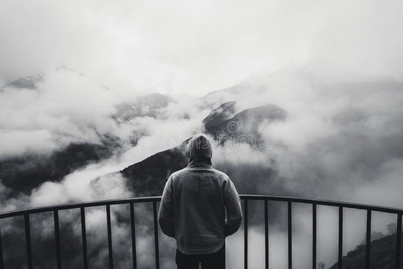 看法从站立在观点的后面一个人看对与有雾的山的美好的风景在距离 黑色和wh 免版税库存照片